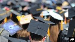 FILE - In this May 5, 2018, file photo, graduates at the University of Toledo commencement ceremony in Toledo, Ohio. Colleges across the U.S. have begun cancelling and curtailing spring graduation events amid fears from the coronavirus.