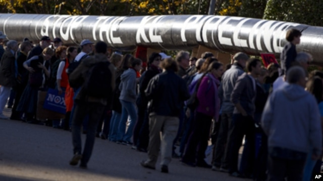 Demonstrators march with a replica of a pipeline during a protest to demand a stop to the Keystone XL tar sands oil pipeline outside the White House,  in Washington, Nov. 6, 2011.