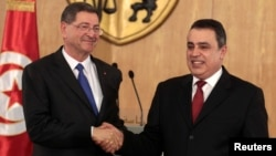 Tunisia's Prime Minister Habib Essid, left, leading a government that combines secular and Islamist parties, shakes hands with his predecessor, Mehdi Jomaa, during a handover ceremony in Tunis, Feb. 6, 2015.