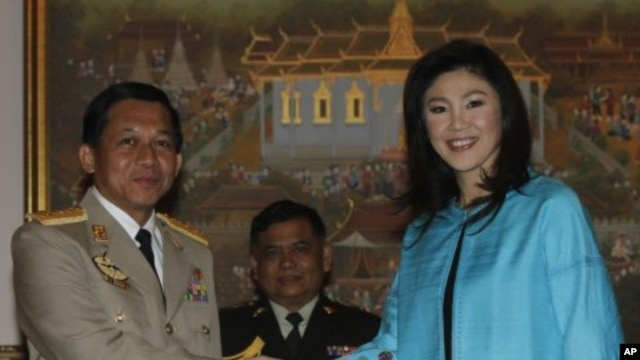 General Min Aung Hlaing (L), Supreme Commander of Burma's armed forces, shakes hands with Thailand's Prime Minister Yingluck Shinawatra during his visit to Thailand, at the Government House in Bangkok, January 10, 2012.