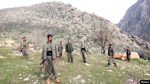 PKK fighters stand guard during the release of eight Turkish prisoners in the northern Iraqi city of Dohuk, March 13, 2013. (Reuters)