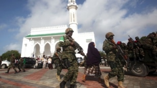 FILE - Soldiers serving in the African Union Mission in Somalia (AMISOM) patrol outside a Mosque during Eid al-Fitr prayers, marking the end of the fasting month of Ramadan at a Mosque in Somalia's capital Mogadishu, July 17, 2015.
