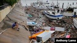 德州居民阿伦·希斯正在观看遭到飓风汉娜破坏的渔船码头。
