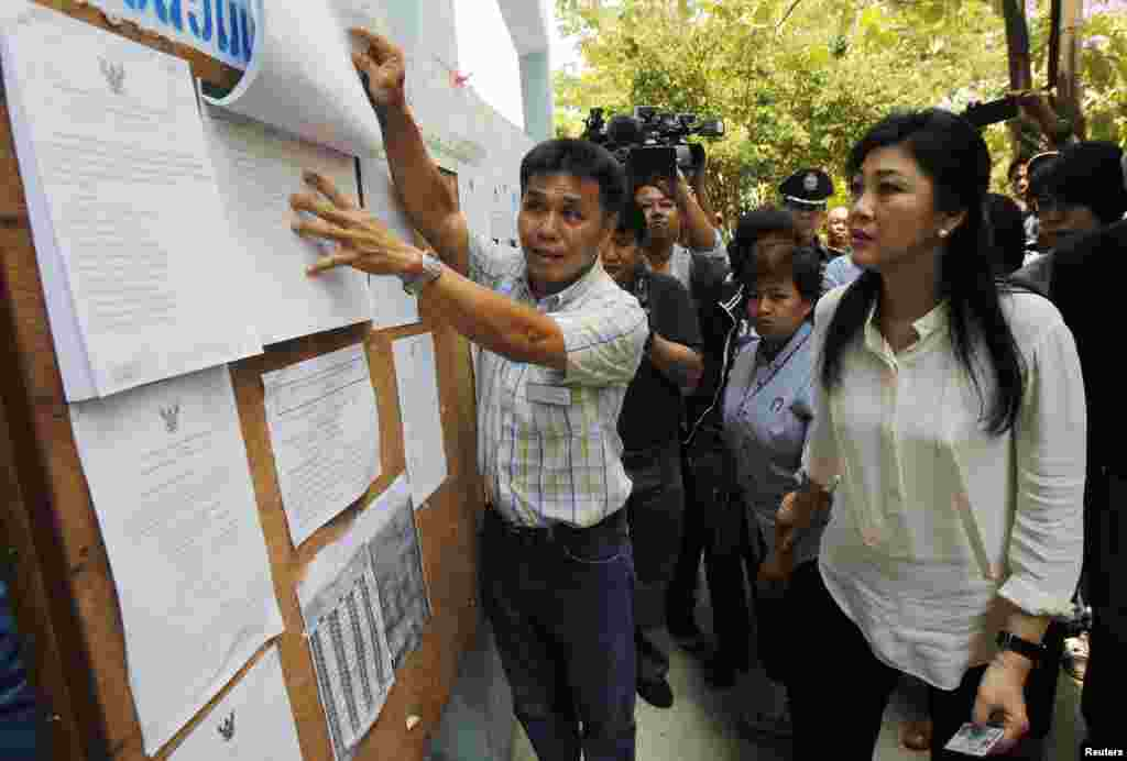 Thai Prime Minister Yingluck Shinawatra, right, checks a list of voters' names before voting at a polling station in Bangkok, March 30, 2014.