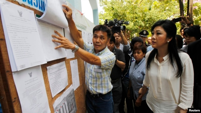 Thai Prime Minister Yingluck Shinawatra (R) checks a list of voters' names before voting at a polling station in Bangkok, March 30, 2014.