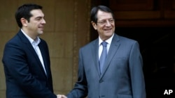 Cyprus' President Nicos Anastasiades, right, shakes hands with Greek Prime Minister Alexis Tsipras at the Presidential Palace following their meeting in the capital Nicosia, Feb. 2, 2015.