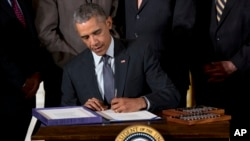 Surrounded by Cabinet officials and members of Congress, President Barack Obama signs H.R. 2146 Defending Public Safety Employees' Retirement Act and H.R. 1295 Trade Preferences Extension Act of 2015 during a ceremony in the East Room of the White House, June 29, 2015.