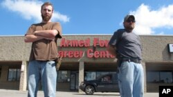 Allen Bowles, left, and Clint Janney, members of the 3 Percent Irregulars Militia, stand guard outside a military recruiting center in Columbus, Ohio, July 21, 2015.