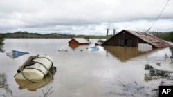 Un granero y equipo agrícola se ven sumergidos en las aguas de la inundación del río Russian en Forestville, California, el miércoles 27 de febrero de 2019.