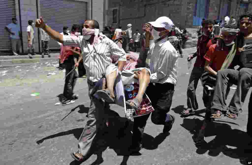 April 5, 2011: Anti-government protestors carry a wounded man during clashes with Yemeni forces in Taiz.