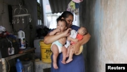 Jaqueline (L), 25, holds her five-month-old twins, Laura (R) and Lucas at their house in Santos, Sao Paulo state, Brazil, April 20, 2016.