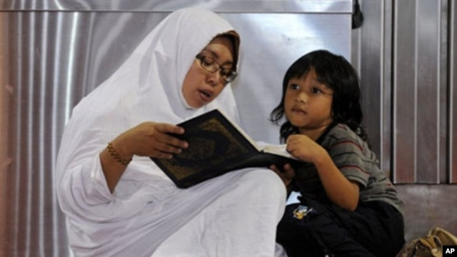 An Indonesian woman reads a copy of the Koran next to a young boy on the first day of the holy Islamic month of Ramadan in Jakarta, 11 Aug 2010