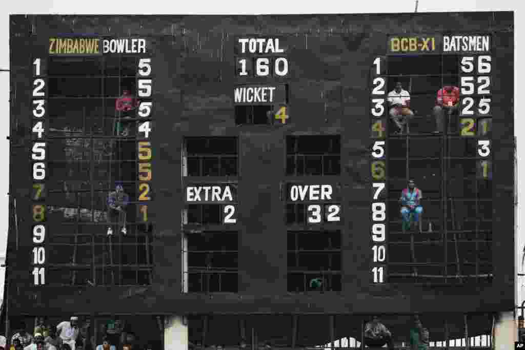 Men sit inside a giant scoreboard to change scores during a warm up match between Zimbabwe and Bangladesh Cricket Board XI in Fatullah, Bangladesh.
