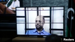 FILE - Saif al-Islam Gaddafi, son of deposed leader Moammar Gadhafi, is seen on a screen via video-link in a courtroom in Tripoli as he attends a hearing behind bars in a courtroom in Zintan, April 27, 2014.