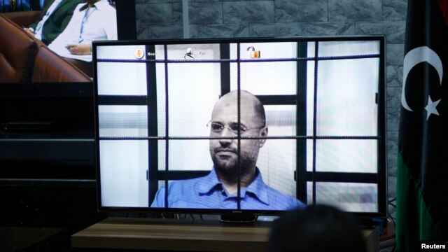 Saif al-Islam Gadhafi, son of deposed leader Muammar Gadhafi, is seen on a screen via video-link in a courtroom in Tripoli, Libya, as he attends a hearing behind bars in a courtroom in Zintan, April 27, 2014.