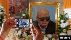 ស្ត្រីម្នាក់ប្រើទូរស័ព្ទ smartphone ថតរូបថតបងធំទី២ នួន ជា នៃរបបខ្មែរក្រហម ក្នុងអំឡុងពេលនៃពិធីបុណ្យសពរបស់លោក ក្នុងខេត្ត ប៉ៃលិន ថ្ងៃទី ៦ ខែ សីហា ឆ្នាំ ២០១៩។ (Reuters)