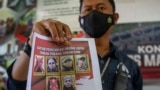 A officer shows a wanted poster displaying two militants Ali Kalora, top left, and Jaka Ramadan, bottom left, in Indonesia, Sept. 19, 2021.