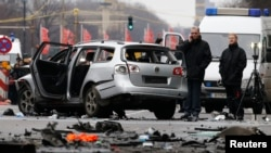 Police inspect the scene of a damaged Volkswagen car in the Bismarckstrasse in Berlin, Germany March 15, 2016. German police said on Twitter that they believe an explosive device caused a car to explode while it was driven along a road in central Berlin o