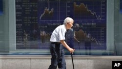 FILE - An elderly man walks by an electronic stock board of a securities firm in Tokyo, Aug. 19, 2016. Elderly healthcare poses significant fiscal challenges all across Asia, experts say.