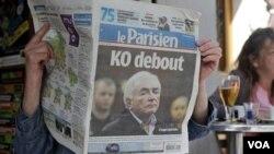 """Una mujer lee el diario franceses """"Le Parisien"""", cuya primera página muestra noticias sobre el director gerente del FMI."""