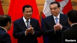 រូបឯកសារ៖ លោកនាយករដ្ឋមន្ត្រី ហ៊ុន សែន ទះដៃជាមួយនឹងនាយករដ្ឋមន្ត្រីចិន លោក Li Keqiang ក្នុងអំឡុងពេលនៃពិធីចុះហត្ថលេខាមួយនៅឯមហាសាលប្រជាជនក្នុងទីក្រុងប៉េកាំង ប្រទេសចិន ថ្ងៃទី២២ ខែមករា ឆ្នាំ២០១៩។