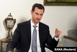 FILE - Syria's President Bashar al-Assad speaks to journalist.