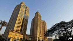 People walk by Sawiris Towers, seven months after president Hosni Mubarak was ousted, and Egypt's business community becomes vocal in its pleas for the interim government to detail how it plans to revive confidence in the economy, in Cairo, Egypt, Septemb
