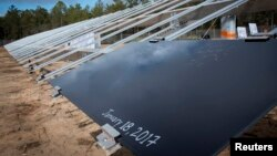 The first of the eventual 375,000 solar panels sits on a rack after a ceremonial initial installation ceremony at Eglin Air Force Base, Florida, Jan. 18, 2017.