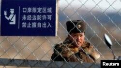 지난 2013년 3월 중국 접경도시 단동과 인접한 북한 황금평에서 북한 병사가 철책을 지키고 있다. (자료사진)
