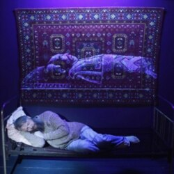 """Artist Vasily Slonov lies on his installation artwork called """"The Terrible Chinese Dream: Death of Mao"""" in the Russian city of Krasnoyarsk last year"""