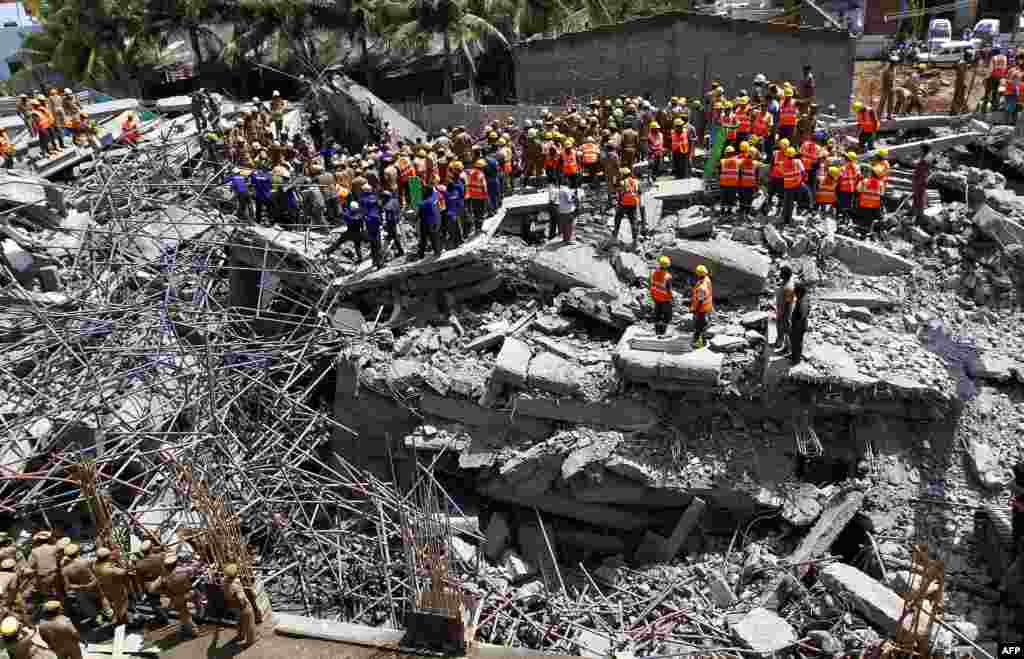 Indian rescue workers look for survivors in the rubble of a collapsed multi-storeyed building in Porur town, situated on the outskirts of Chennai. At least nine people were killed and dozens feared trapped after an 11-storey residential block crumbled, officials said.