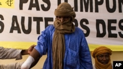 Alhader Ag Almahmoud, a 30-year-old Tuareg herder whose right hand was amputated last month by an Islamist group imposing their interpretation of Shariah, displays his bandaged arm at an Amnesty International press conference in Bamako, Mali, September 20.