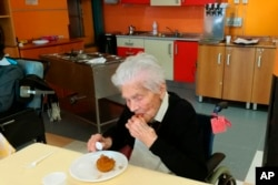 "In this photo taken on April 6, 2020, 103-year-old Ada Zanusso, eats her meal at the nursing home ""Maria Grazia"" in Lessona, northern Italy, after recovering from Covid-19 infection. (Residenza Maria Grazia Lessona via AP Photo)"