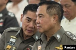 FILE - The next Thai national police chief Chakthip Chaijinda (L) talks with Thai national police chief Somyot Poompanmuang (R) during a religious ceremony near the Erawan shrine in central Bangkok, August 21, 2015.