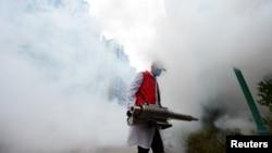 یک داوطلب در حال ضدعفونی کردن محوطه یک مجموعه مسکونی در شهر گانژوو، چین - ۶ فوریه ۲۰۲۰
