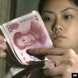 A Chinese bank worker displays Chinese yuan at a bank in a Beijing (File Photo)