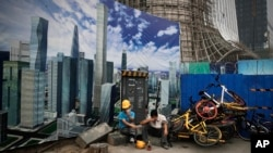ILE- In this June 26, 2018, file photo Chinese workers take a break outside a construction site wall depicting the skyscrapers in the Chinese capital at the Central Business District in Beijing.