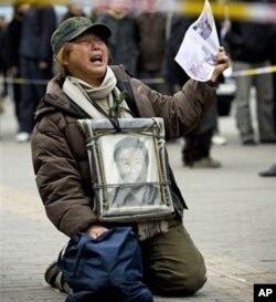 中国的一位访民手持上访信下跪伸冤(资料照片)