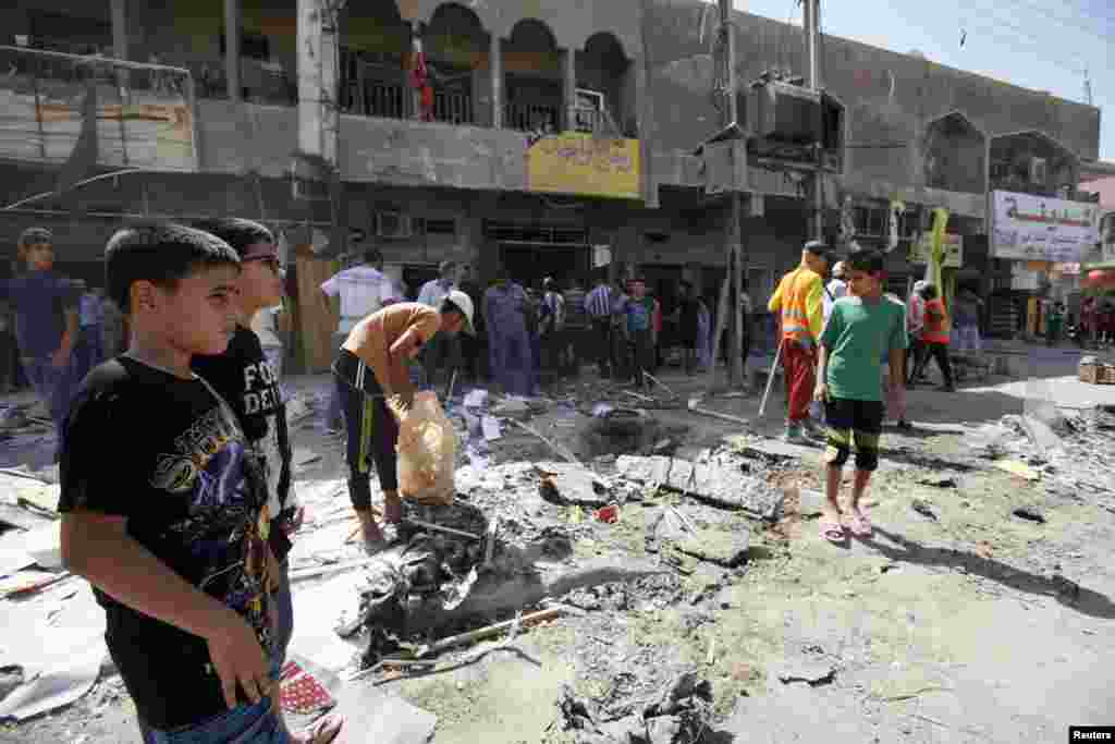 Youths look at the site of a car bomb attack in Baghdad's al-Shaab district, August 28, 2013.