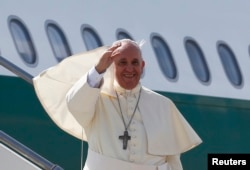 Pope Francis waves as he boards his plane to leave for his pastoral visit to South Korea, at the Fiumicino airport in Rome, Aug. 13, 2014.