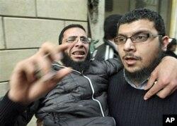 Des manifestants évacuant un blessé de la Place Tahrir, au Caire