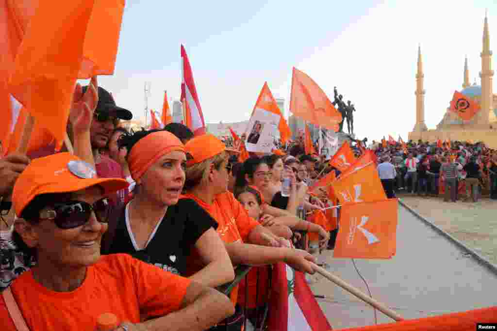 Supporters of the Free Patriotic Movement (FPM) carry flags during a protest in Beirut, Lebanon. Thousands rallied to support a leading Christian politician's call for a presidential election, in the midst of a political crisis that has paralyzed the government and parliament.