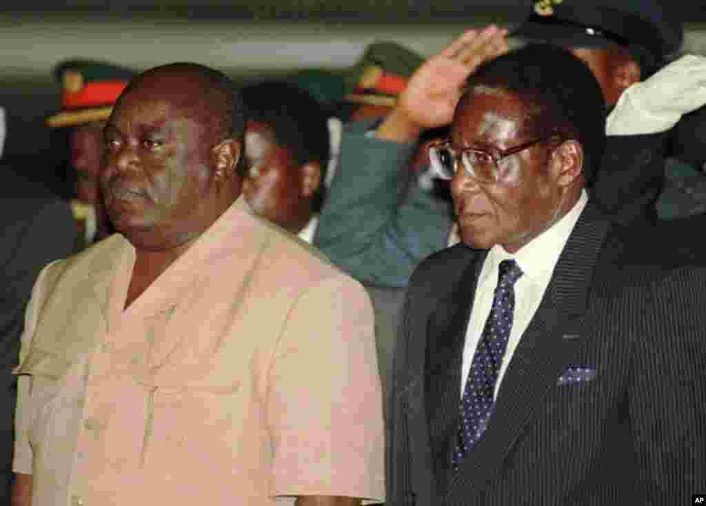Le président congolais Laurent Kabila, à gauche, est accueilli par le président zimbabwéen Robert Mugabe à l'aéroport international d'Harare, le 1er juin 1997.