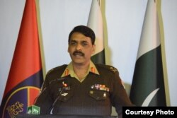 FILE - Major-General Asif Ghafoor holds a press briefing, Dec. 27, 2017, in this his handout picture made available by Pakistan's Army's media wing, ISPR.