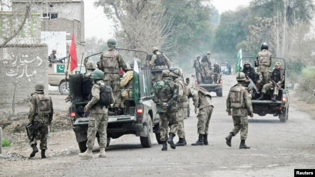 Soldiers arrive and take position near the site of a police station after it was attacked in Bannu, February 14, 2013.