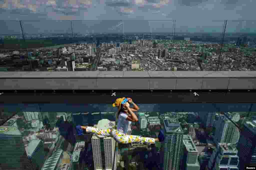 ស្ត្រីម្នាក់ពាក់ម៉ាសមើលសូរ្យគ្រាសនៅលើកញ្ចក់សម្រាប់មើលទេសភាព Mahanakhon Skywalk Glass Tray នៃអគារ King Power Mahanakhon នៅក្នុងក្រុងបាងកក ប្រទេសថៃ។