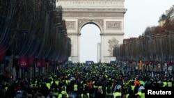 """ພວກປະທ້ວງພາກັນໃສ່ເສື້ອກັກສີເຫຼືອງ ຍ່າງໄປຕາມເສັ້ນທາງ Champs-Elysees ໂດຍມີ Arc de Triomphe ຢູ່ໃນດ້ານຫຼັງ ໃນລະຫວ່າງ ວັນປະທ້ວງແຫ່ງຊາດ ໂດຍເອີ້ນວ່າ ຂະບວນການ """"ເສື້ອກັກສີເຫຼືອງ"""" ໃນນະຄອນຫຼວງ ປາຣີ, ວັນທີ 8 ທັນວາ 2018."""