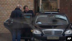 FILE - Former Russian defense minister Anatoly Serdyukov (R) is seen getting into a car in Moscow, Russia, Dec. 6, 2013. Spanish prosecutors suspect Serdyukov of having ties to the criminal underworld.