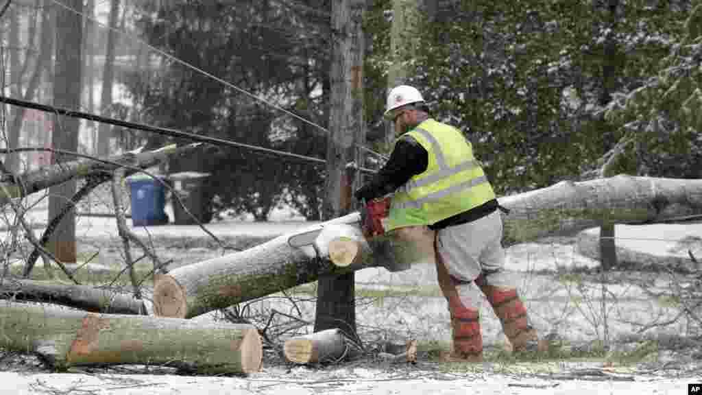 Un travailleur de Duke Energy, compagnie électrique, utilise une tronçonneuse pour couper un arbre tombé sur des lignes électriques à Matthews, Caroline du Nord, 22 janvier 2016.