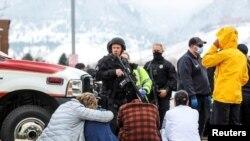 Policías fuertemente armados vigilan a personas evacuadas del supermercado King Soopers en Boulder, Colorado, donde un sujeto disparó indiscriminadamente matando a diez personas.